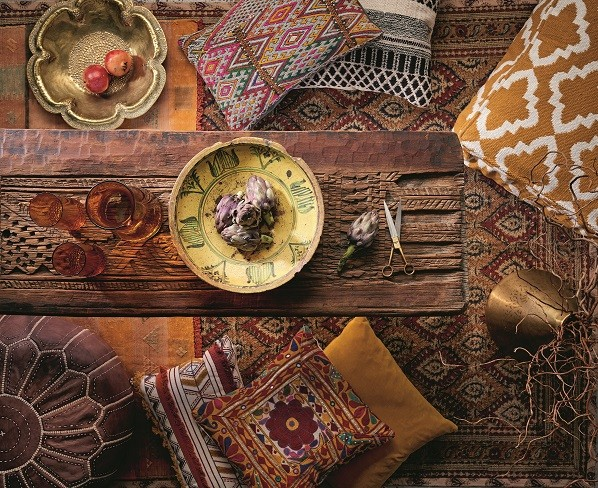 A Moroccan-style table surrounded by ornate floor cushions and gold bowls of pomegranates