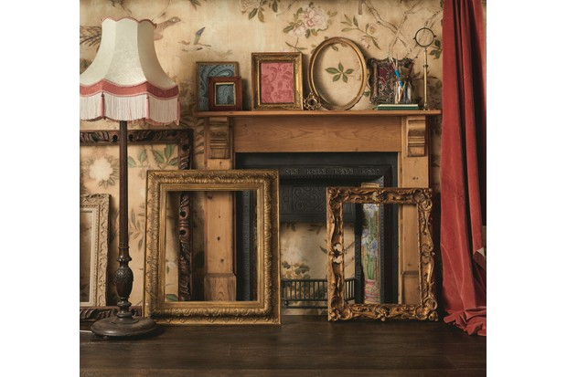 Antique frames leant against a wooden fire surround next to an antique fringed lamp.