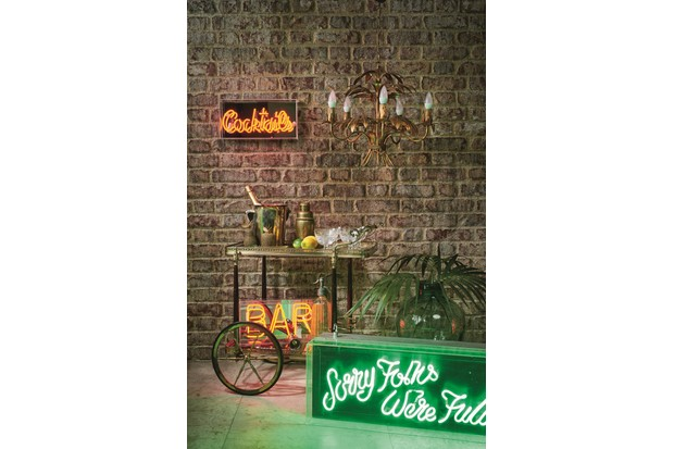 A vintage drinks trolley surrounded by neon lights and decorated with vintage glassware.