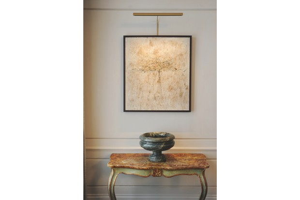 Picture light in gold powder-coated finish above a pencil sketch