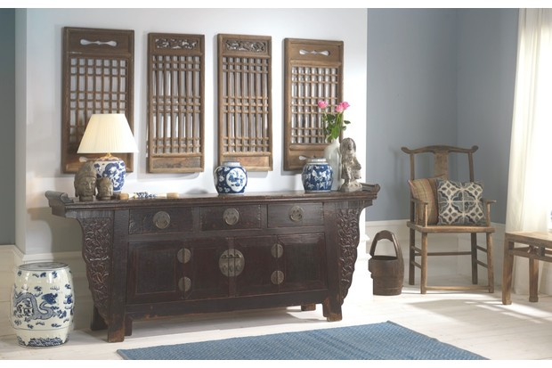 A wide hallway with an oriental-style sideboard flanked by ceramic table lamps and a set of four antique shutters
