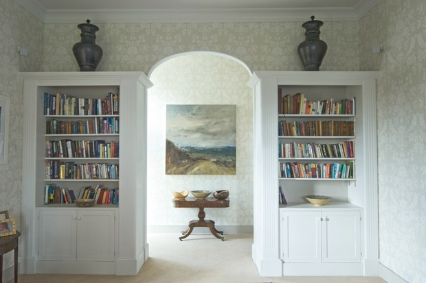 An archway flanked by matching white bookcases