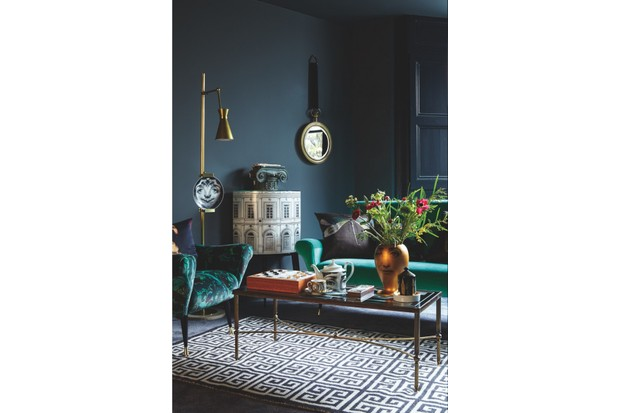 A dark grey living room featuring a green velvet sofa and armchair, plus Fornasetti plates and a Fornasetti drinks cabinet