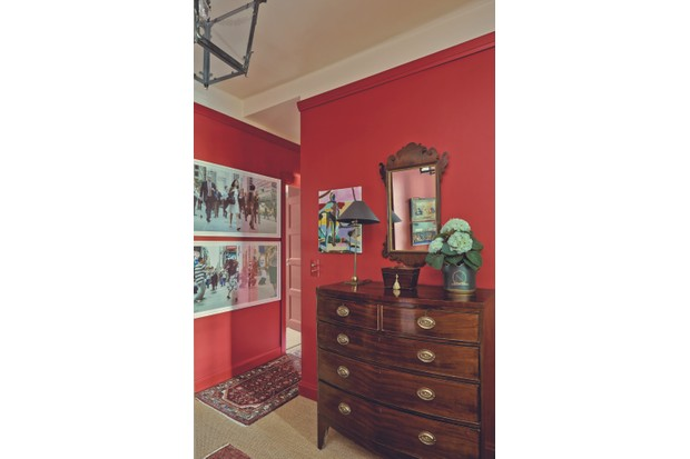 A Georgian bow-fronted chest of drawers against a deep scarlet-coloured wall