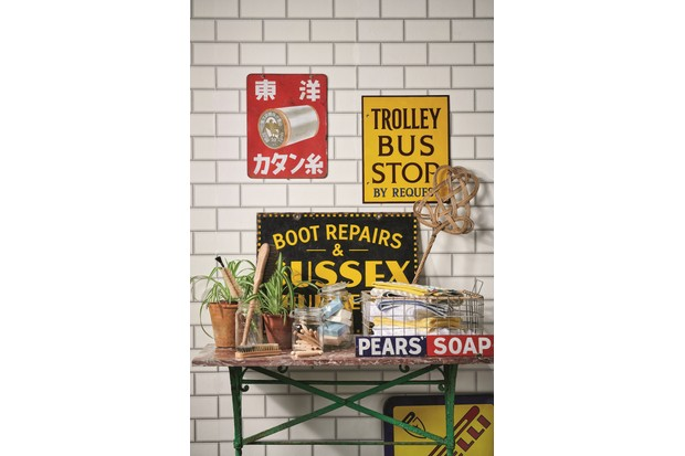 An array of vintage signs in a utility room decorated with white metro tiles.