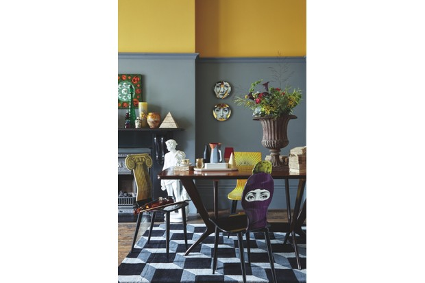 A two-tone yellow and grey dining room with a large dining table and Fornasetti dining chairs