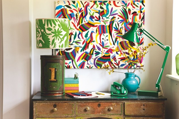 A colourful hand-embroidered artwork above a vintage storage unit with a green anglepoise lamp