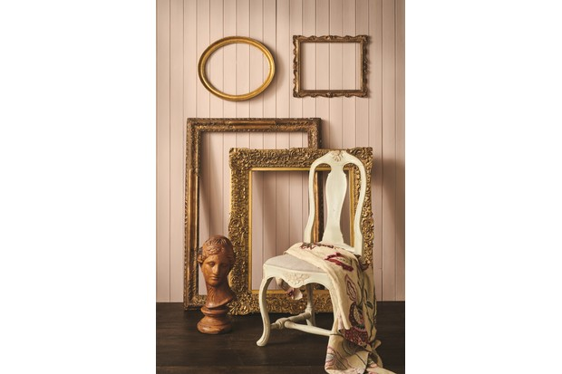 Oversized gold frames leant against a blush pink wall with a washed white chair.