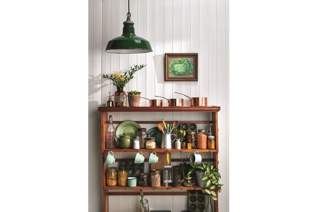 A vintage shelving unit is used to display copper pans and jars of larder essentials in a kitchen.