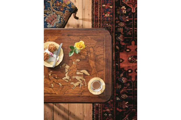 A traditional marquetry coffee table on an antique Persian rug