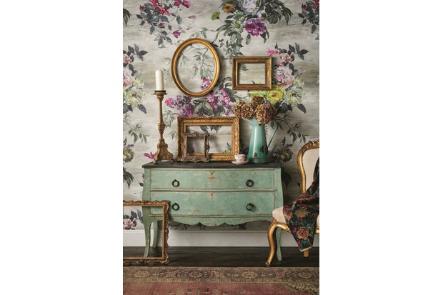 An antique commode against statement floral wallpaper, gold frames in different sizes sit atop the commode.