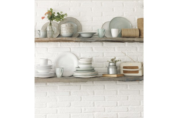 Rustic wood shelves adorned with pale-coloured plates, dishes and mugs on an exposed brick wall painted white