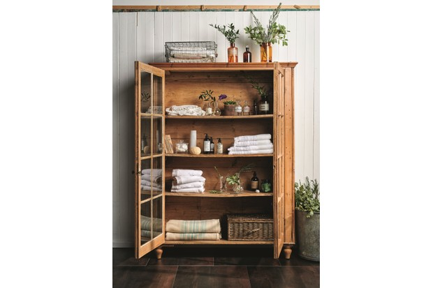 A glass-doored vintage display cabinet is used to show off towels, toiletries and plants in a bathroom.