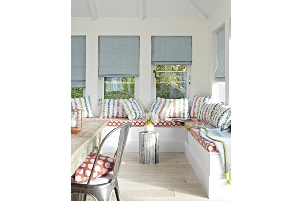 A white extension with built-in seating and blue roller blinds