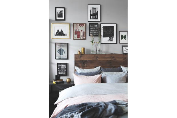 A gallery wall of prints and photographs hanging above a double bed with a rustic wooden headboard