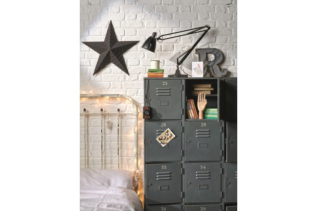 A grey vintage metal locker is used as a bedside table to a distressed metal bed.
