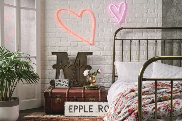 An industrial bedroom with a copper bed frame and a vintage trunk as a bedside table. There are heart-shaped neon lights on the wall.