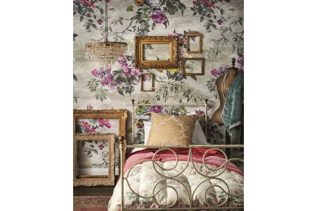 A vintage metal single bed against bold floral wallpaper. A cluster of antique frames is displayed above the headboard.