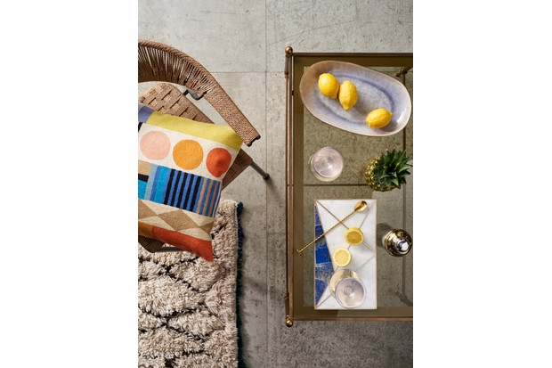 A gold and glass coffee table topped with studio ceramics and metallic cocktails accessories