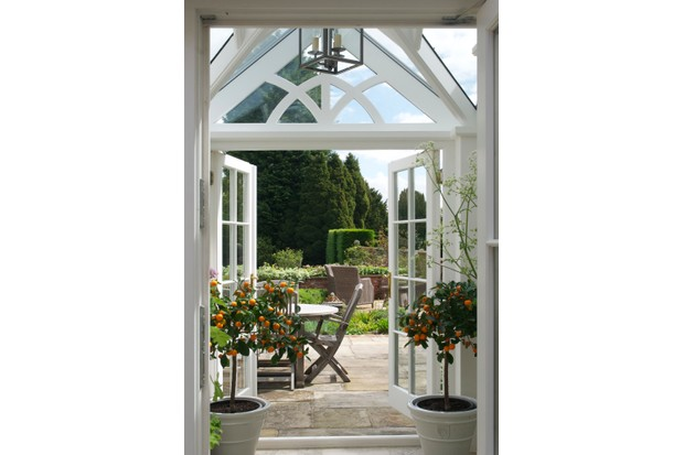 White patio doors flanked with small orange trees, looking out onto a garden in full bloom