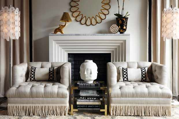 Two fringed armchairs flank an Art Deco fireplace
