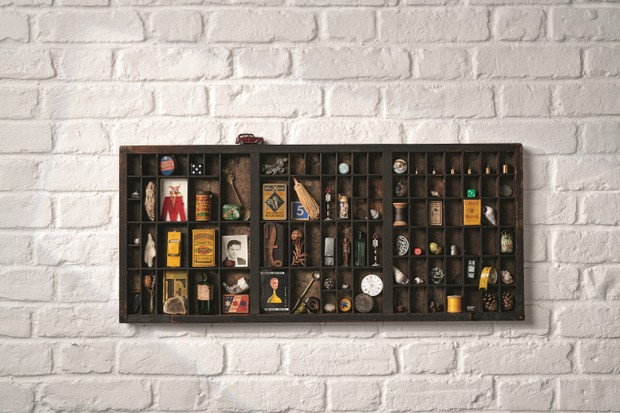 An antique printers tray is mounted on the wall and used to display a collection of small curios
