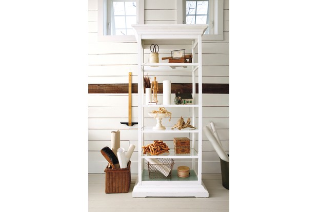 A white medical-style glass cabinet filled with antique and vintage curios