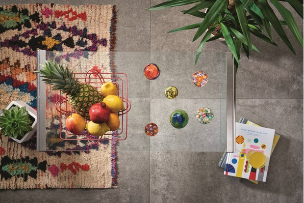 A glass coffee table arranged with a wire basket of tropical fruit and glass paperweights
