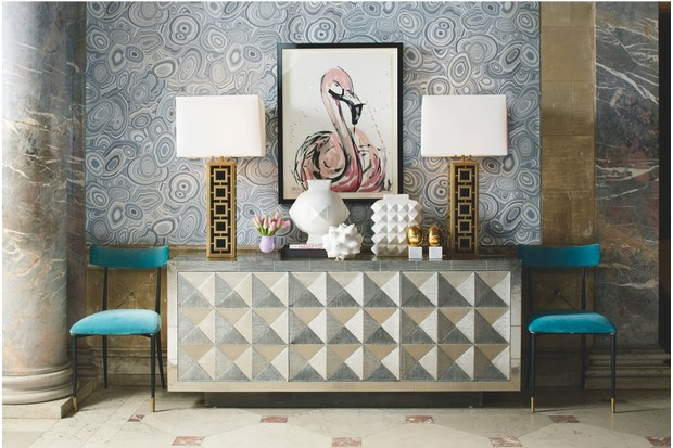 A bold geometric sideboard flanked with blue velvet dining chairs and gold table lamps. A sketch if a flamingo is in the centre.