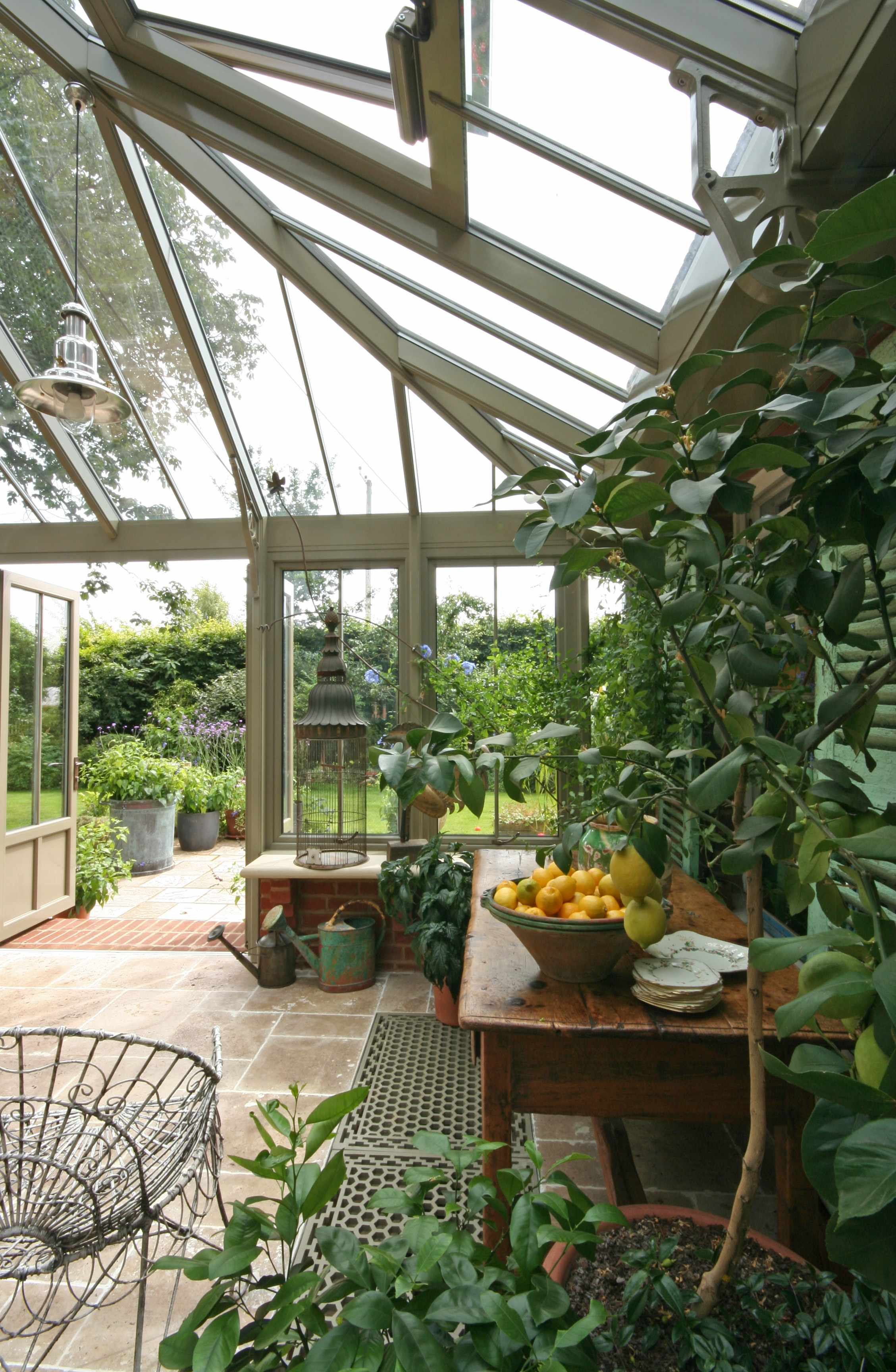 This powder-coated aluminium conservatory is furnished with rustic and weathered finds. Prices for similar garden rooms by Marston & Langinger start from around £50,000.