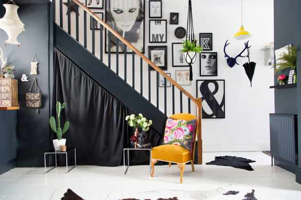 A large gallery wall of black and white prints lining a staircase