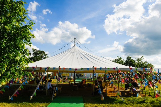 An open-sided tent at the Hay festival, covered in multi-coloured bunting