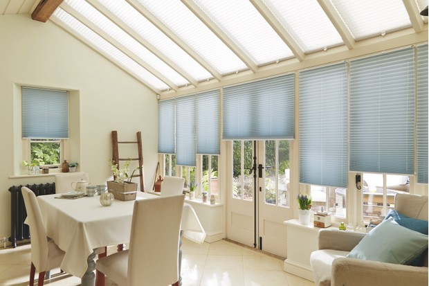 A lean-to conservatory with blue pleated roof blinds