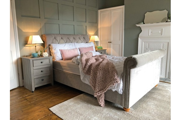 A blush pink bed against a panelled sage green wall