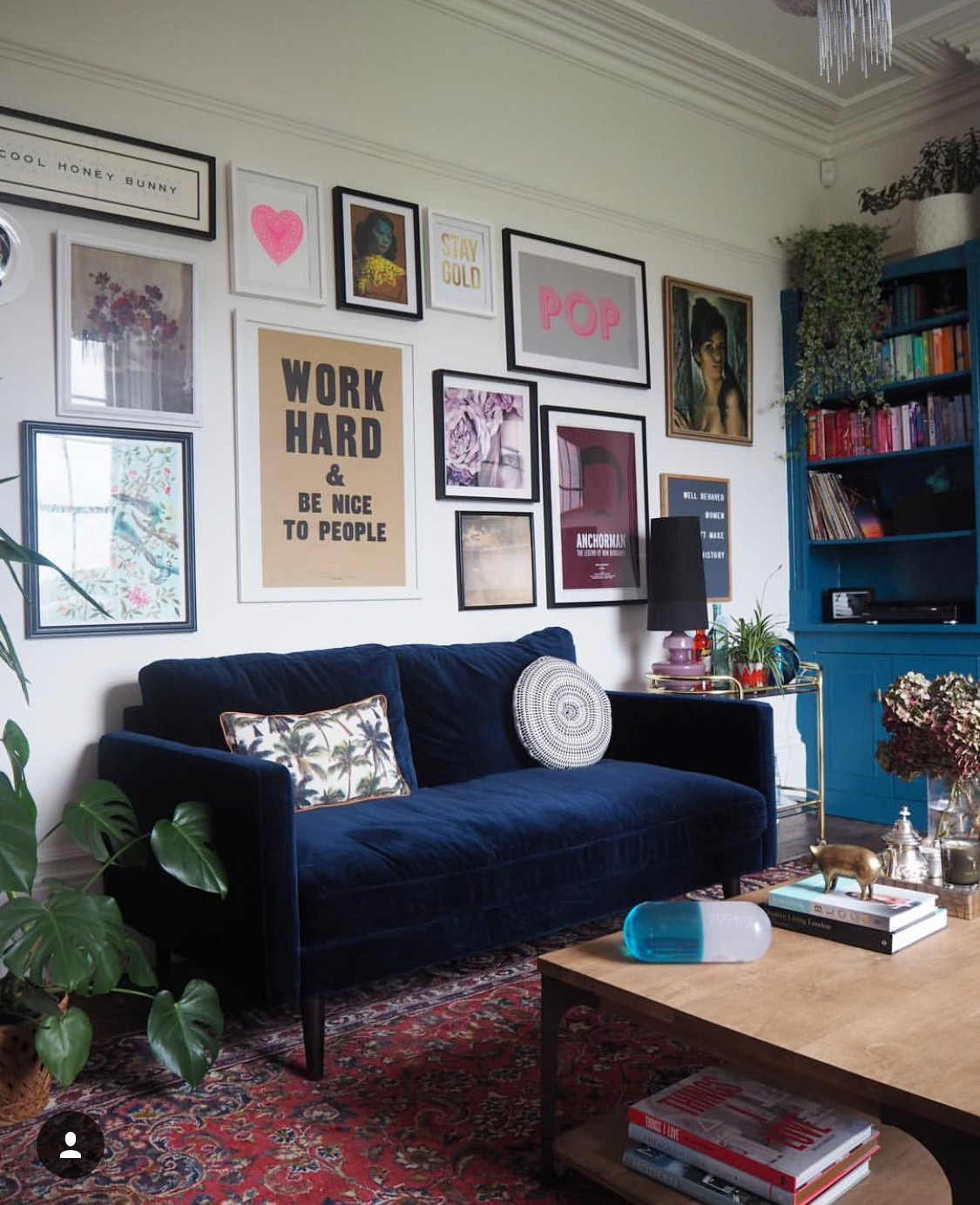 A blue velvet sofa on an antique Persian rug in front of a gallery wall