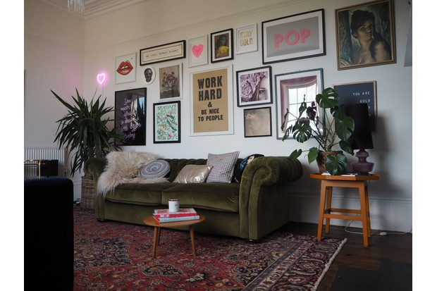 A green velvet Chesterfield sofa flanked by house plants