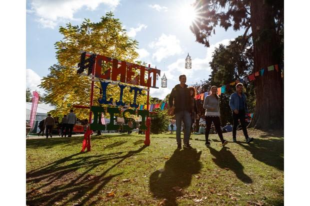 Festival-goers stroll alongside a large sign for the Cheltenham Literature Festival