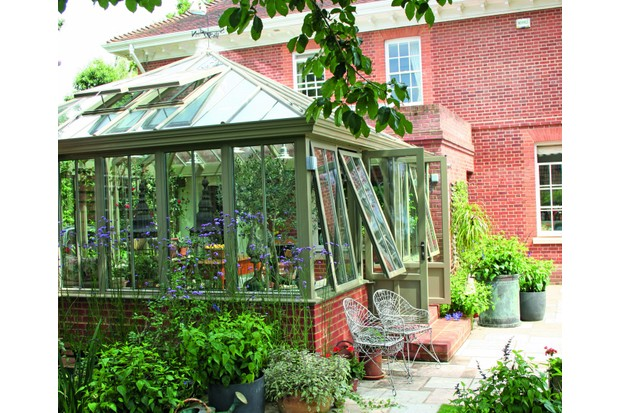 A Victorian-style conservatory filled whith plants on a red brick house