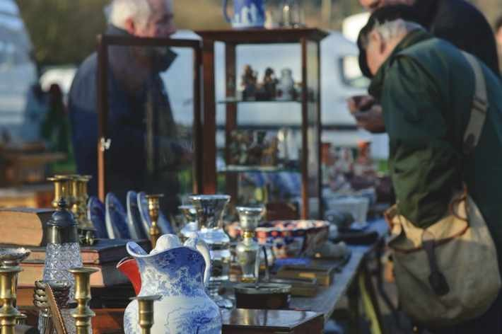 A man in a flat cap browses a stall of antique curios at a flea market