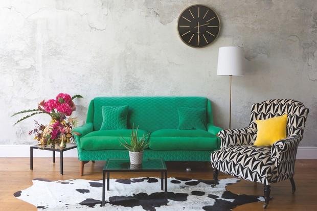 A bright green sofa on a cowhide rug, alongside a geometric print occasional chair.