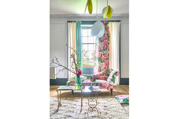 An elegant chaise upholstered in bold pink and green floral fabric.