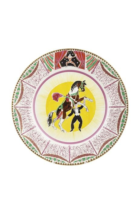 A colourful circus-themed dinner plate picturing a decorated horse and handler