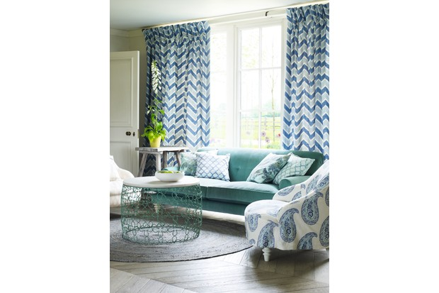 A teal velvet sofa infront of zigzag print blue curtains