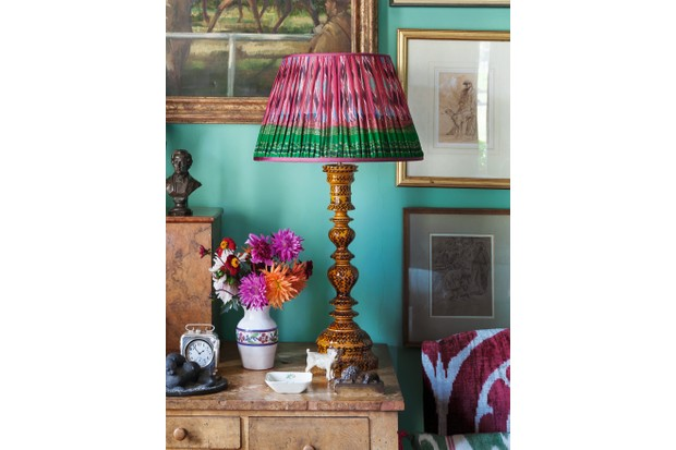 A ruched lampshade on a wooden table lamp against a teal coloured wall