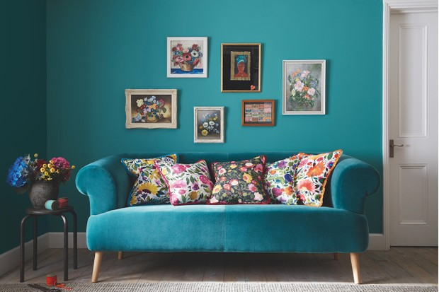 A bright teal sofa in front of a wall of the same colour.
