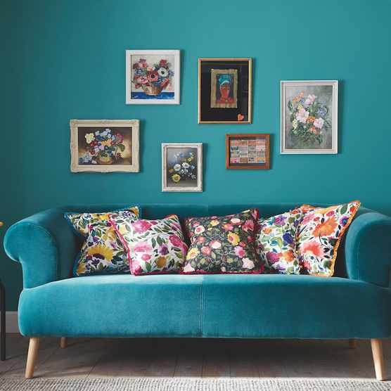 Sofa in plain velvet, £54 per m; cushions (from left to right) in Isabelle's Garden; Rosina; Tatiana; Giselle; and Rosina linen, £42 per m for linen, £45 per m for velvet. All from the Artbook by Kim Parker collection at Clarke & Clarke.