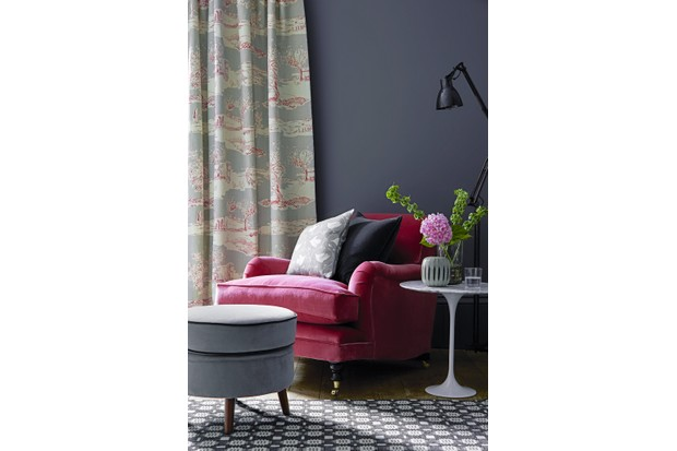 A relaxed armchair upholstered in rose velvet.