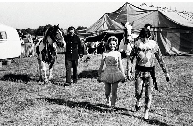 23rd July 1949: Sixteen-year-old Ella Freeman, who performs under the stage name of Ella Clarissa the Ballerina is one of the most popular acts in Lord George Sanger's Circus. Here she approaches the Big Top with her Harlequin partner, prior to a daring two-horse pas-de-deux. Original Publication: Picture Post - 4837 - The Little Circus Queen - pub. 1949 (Photo by Bert Hardy/Picture Post/Getty Images)