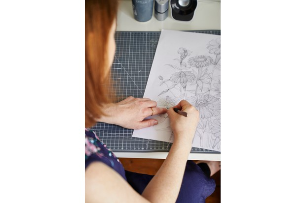 Jessica Baldry sketching out a botanical design before cutting it out