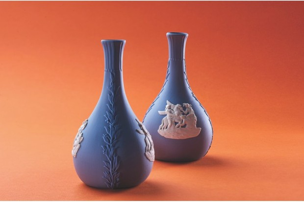 Two blue Wedgwood Jasperware vases shot against a burnt orange background